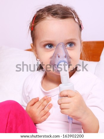 Little girl making aerosol treatment with a rubber mask