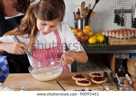 Little girl making cake dough in the kitchen