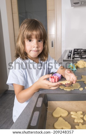 Little girl making cookie dough looking at camera