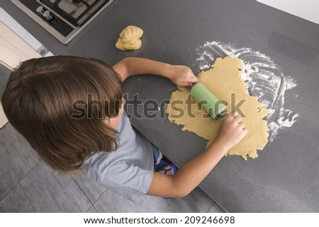Little girl making cookie dough seen from above - stock photo