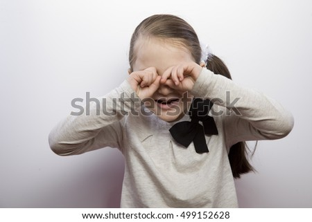 little girl making faces. acting, depiction of different emotions. the development of emotional intelligence. sad face, the child cries, covers her face with hands