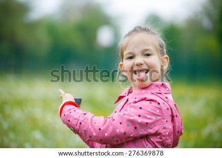 Little girl making faces and showing her tongue to her father that disturbed her at taking a picture with smart phone. Disobedience, cheerful behavior and carefree childhood concept.  - stock photo