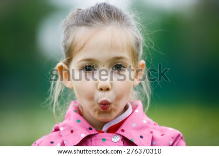 Little girl making faces for the camera on a hiking trip with her family. Disobedience, cheerful  behavior and carefree childhood concept.  - stock photo
