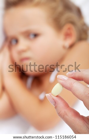Little girl making faces to her medication - focus on the pill - stock photo