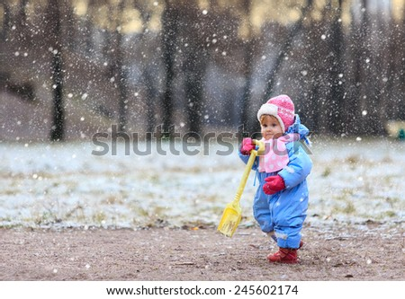 little girl making first steps in snow winter park - stock photo
