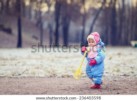 little girl making first steps in winter park - stock photo