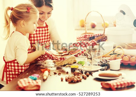 Little girl making gingerbread with her mom. Preparation for Christmas.