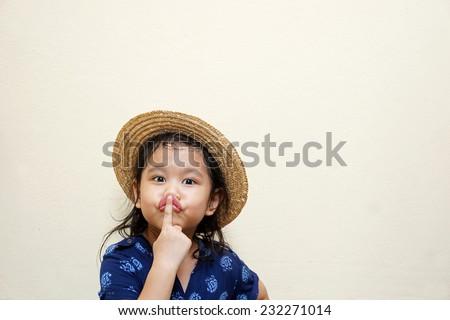 Little girl making keep quiet gesture - stock photo