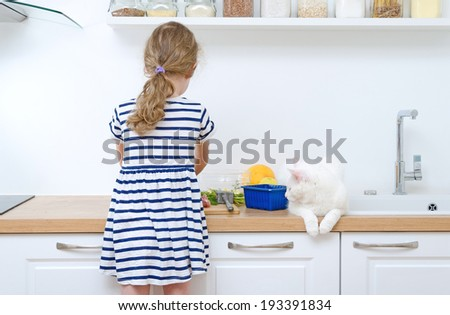 Little girl making meal in the kitchen. - stock photo