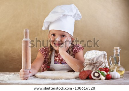 Little girl making pizza - preparing the dough and other ingredients - stock photo