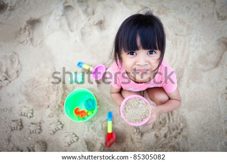 Little Girl Making Sand on the Beach - stock photo