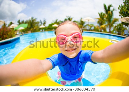 Little girl making selfie at inflatable rubber ring having fun in swimming pool - stock photo
