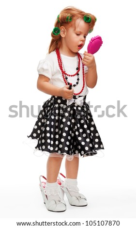 Little girl making up her face with lipstick, playing with mothers things - stock photo