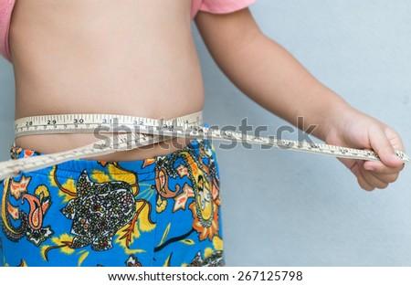 Little girl measuring her stomach - stock photo