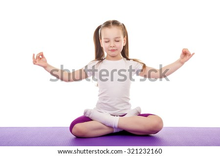 Little girl meditates, sitting in lotus position
