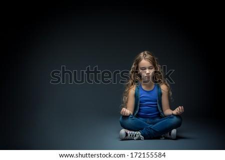 Little girl meditating in lotus position - stock photo
