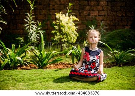 little girl meditating in the nature, yoga - stock photo