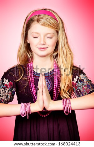 Little girl meditating over pink background.