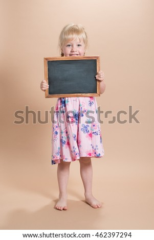 Little girl of pre-school age holding chalk board - chalkboard left blank to add your own message