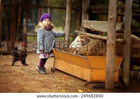 little girl on a farm with animals - stock photo