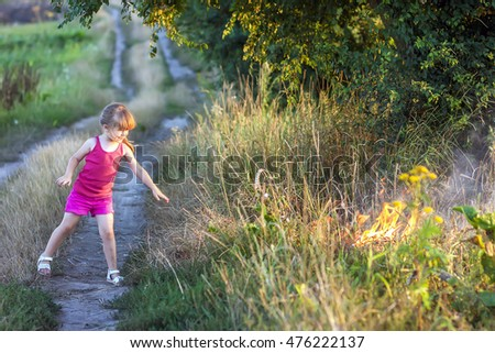 Little girl on a field road playing with fire