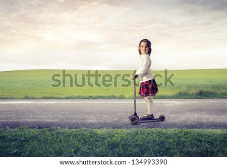 little girl on a scooter on the road in the country - stock photo