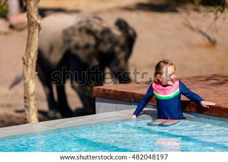 Little girl on African safari vacation enjoying wildlife viewing standing near swimming pool