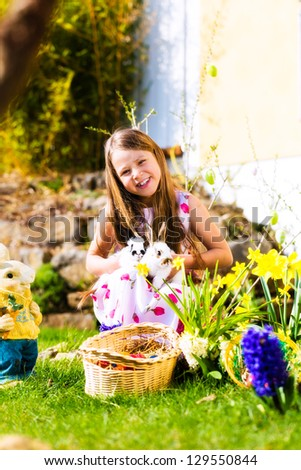 Little girl on an Easter Egg hunt on a meadow in spring, she holds two living Bunnies - stock photo