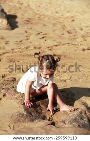 Little girl on beach sitting on stone - stock photo
