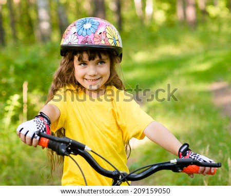 little girl on bike in forest looking at camera and smiling - stock photo