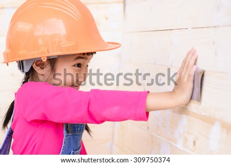 Little girl on carpenter jobs surprise with sanding on wood