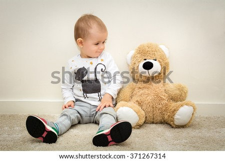 little girl on carpet in room with large teddy bear looking down lonely - stock photo