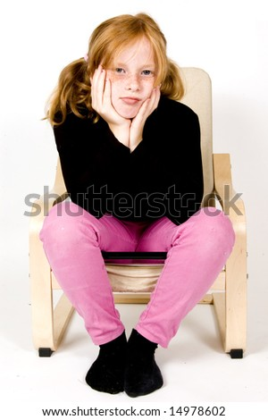 little girl on chair is looking bored