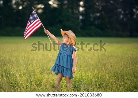 Little girl on  field with American flag.