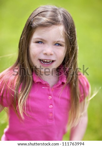 Little girl on grass on a windy day