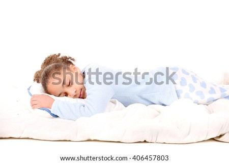 little girl on her pajamas in bed isolated in white