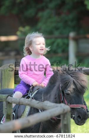 little girl on horseback - stock photo