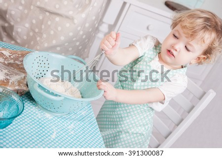 Little girl on kitchen kneads dough