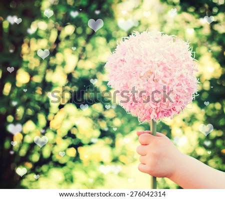 little girl on mothers day - with flowers ands hearts at background - stock photo