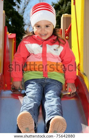 Little Girl on Playground Ready to Slide Down