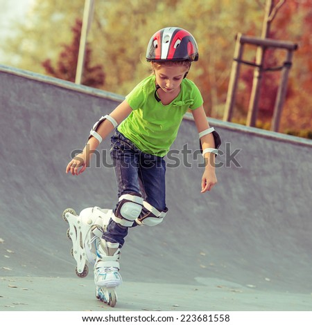 Little girl on roller skates in helmet at a park - stock photo