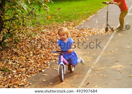 little girl on runbike and boy at scooter in autumn, kids sport