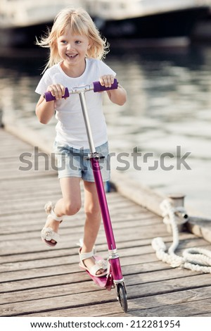 Little girl on scooter near the sea - stock photo