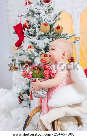 Little girl on sledge under the Christmas tree