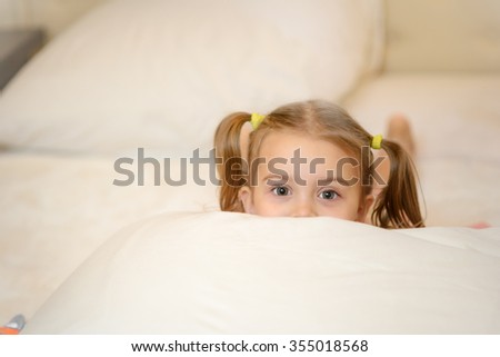 Little girl on the bed at home among the pillows