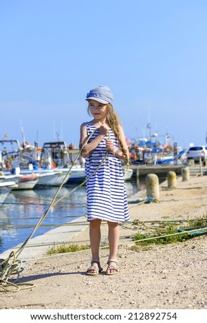 Little girl on the harbor holding a rope - stock photo