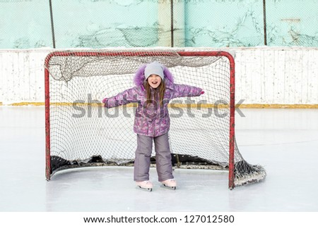 little girl on the hockey ice field in the gate