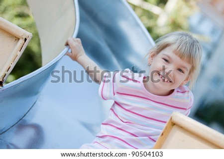 Little girl on the playground having fun at summer time.