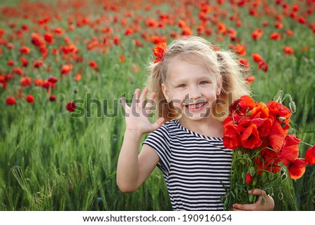 Little girl on the poppy meadow greeting waving her palm - stock photo