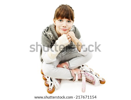 Little girl on the rollerblades with broken arm, sitting. Isolated on white background  - stock photo